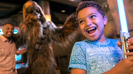 An excited young boy smiling while he ignites a toy lightsaber, as his dad poses alongside Chewbacca
