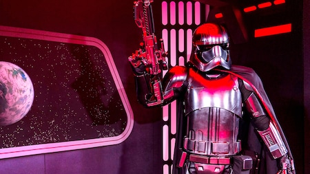 Captain Phasma holds her weapon pointed upward in her right hand
