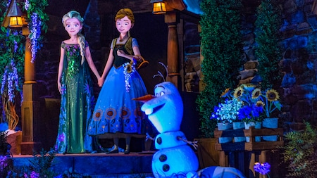 Anna et Elsa se tiennent par la main, avec Olaf qui se trouve à proximité