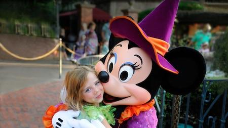 Minnie Mouse porte un costume de sorcière et serre dans ses bras une petite fille habillée en Fée Clochette