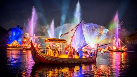 Un artiste se tient sur un bateau, des fontaines d'eau jaillissent dans les airs et des images sont projetées sur un écran de bruine