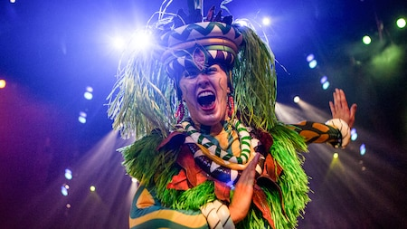 A festively costumed performer roars during Festival of the Lion King at Disney's Animal Kingdom park