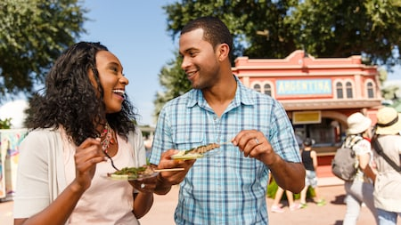A couple smiles while indulging in Argentinian fare at the Epcot International Food & Wine Festival