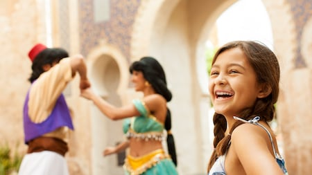 A young female Guest smiling excitedly while Aladdin & Jasmine enjoy a dance at the Morocco Pavilion