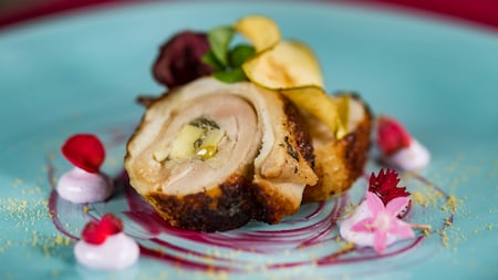 Pork roulade garnished with sauce, cream and flower petals
