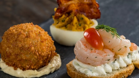 A Scotch egg, a devilled egg topped with bacon and sliced bread topped with sauce, shrimp, dill and a cherry tomato