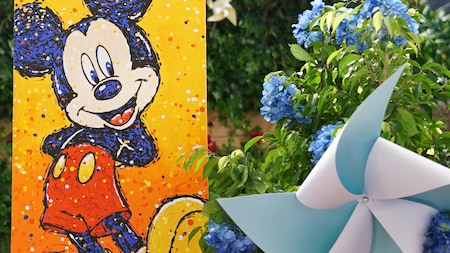 A stylized painting of Mickey Mouse is displayed amongst lush foliage dotted with pinwheels