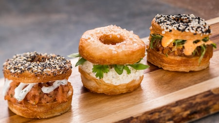 3 cronuts topped with sugar and seeds and filled with salmon, cheese, parsley, pork, peppers and cream