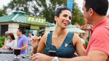 Un homme et une femme se sourient en dégustant de la nourriture et du vin au pavillon de l'Italie
