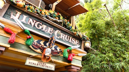 Tropical holiday decorations adorn the tiki-style sign near the entrance to the Jingle Cruise
