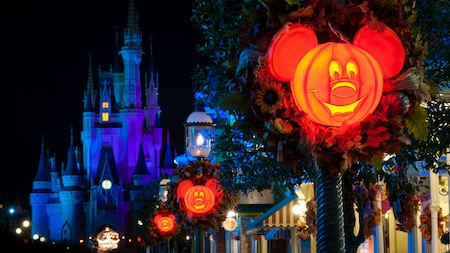 glowing mickey mouse themed pumpkin lanterns line the streets outside cinderella castle - Halloween In Orlando Fl