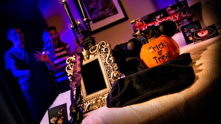 Duas crianças veem presentes de Halloween, incluindo um espelho com Vilões Disney esculpidos e uma abóbora de brinquedo