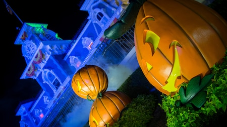 3 happy jack o lanterns sit in a pumpkin patch in front of the train station on Main Street U.S.A