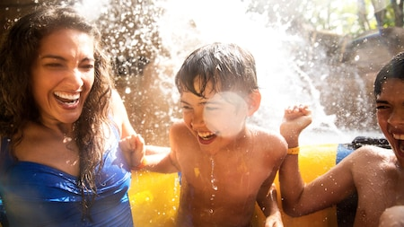 A mom and her sons laugh while enjoying a tube-based attraction at Disney's Typhoon Lagoon water park
