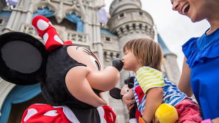 A mother holds her young daughter who kisses Minnie Mouse's nose outside Cinderella Castle