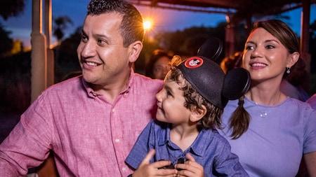 Un hombre y una mujer sonríen mientras sostienen a un niño usando orejas de Mickey