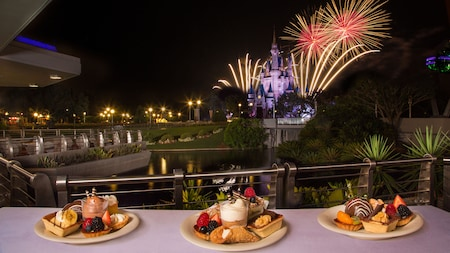 Various deserts on a table on a balcony with a view of fireworks bursting in the sky over Cinderella Castle