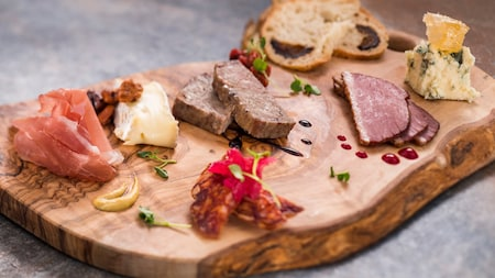 A wooden board topped with cheese and assorted charcuterie