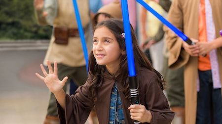 A young girl holding a lightsaber attempts to wield the Force at Jedi Training: Trials of the Temple