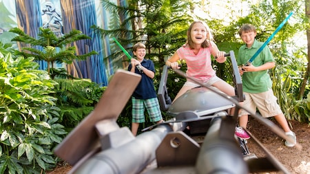 A girl sits atop a speeder while 2 boys play with lightsabers at Star Tours – The Adventures Continue