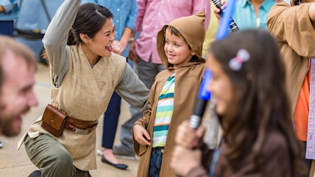 A boy smiles while receiving instruction from a Jedi Knight during Jedi Training: Trials of the Temple