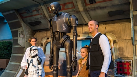 A family dressed up in Star Wars-themed attire stand next to K2SO