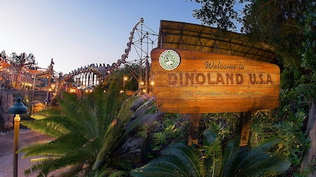 A dinosaur skeleton near ferns and a sign that reads Welcome to Dinoland U.S.A. The Friendliest Fossils in America