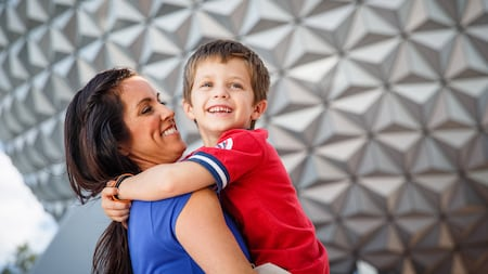 Una mujer sostiene a un niño sonriente, frente a Spaceship Earth