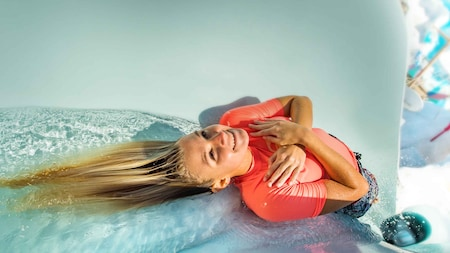 A woman slides down a water slide