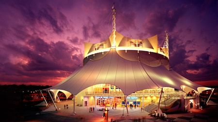 A large circus tent attached to a structure near clusters of people