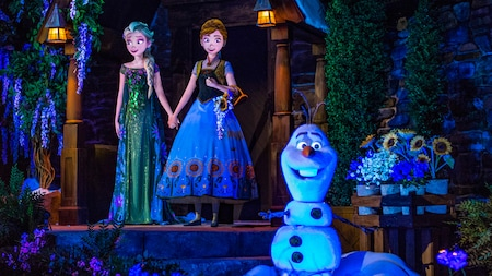 Elsa, Anna and Olaf from the movie Frozen stand in front of a stone building