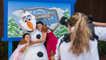 Two girls hug Olaf while a woman takes a picture