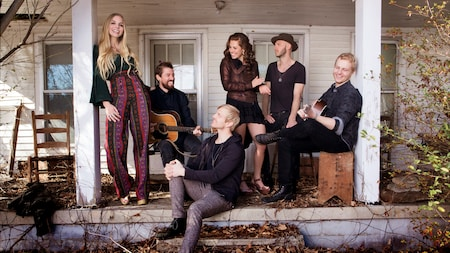 The 6 members of American folk rock band Delta Rae hang out on the porch of an old house
