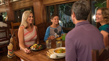 A family of 4 eats an evening meal in a restaurant dining room