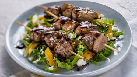 3 beef skewers rest on a bed of salad that contains fruit and cheese