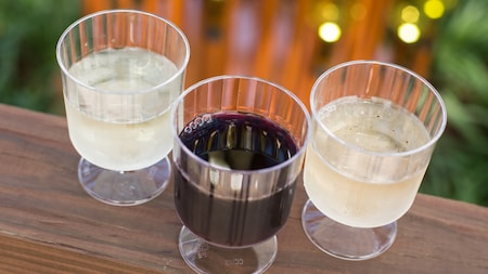 3 plastic glasses containing wine samples