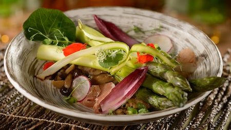 An asparagus and prosciutto salad with endive and olives in a bowl