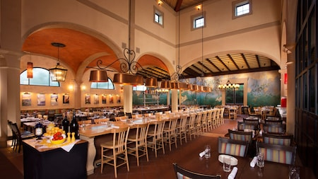 Dining area with private tables and a long table in the center of the room with family-style seating