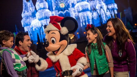 Santa Mickey holding hands with a family dressed for the season as lights shine on Cinderella Castle