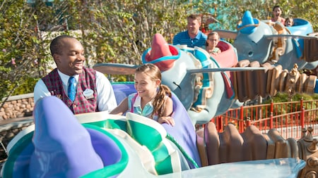 A VIP Tour Guide riding with a young female Guest while they both enjoy Dumbo the Flying Elephant