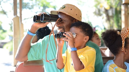 A father and his young son look through their own pairs of binoculars while enjoying a safari tour