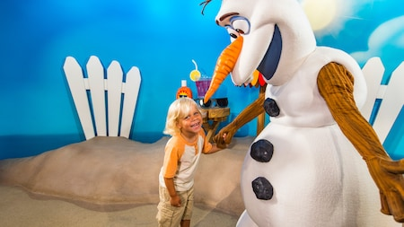 A boy enjoying a Character Greeting experience with Olaf from 'Frozen' at Disney's Hollywood Studios