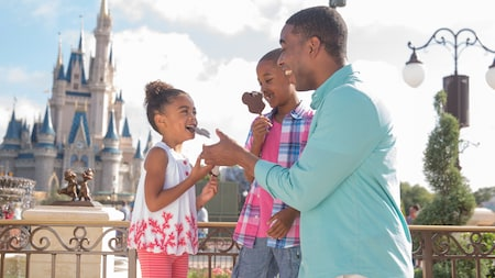 A dad, daughter and son enjoying Mickey ice cream bars near Cinderella Castle at Magic Kingdom park