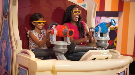 A woman and a little girl smile as they ride Toy Story Midway Mania!