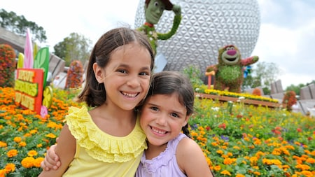 Two girls smiling beside the topiaries near Spaceship Earth at Epcot
