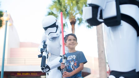 A smiling boy holds a lightsaber near 2 stormtroopers