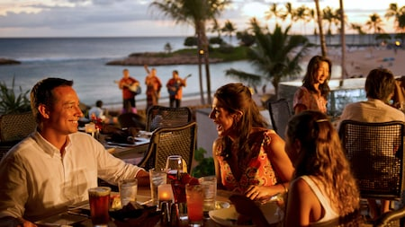 Families dining on a beachside patio at Aulani Resort