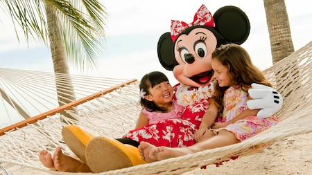 Two young girls lounging in a hammock on the beach with Minnie Mouse