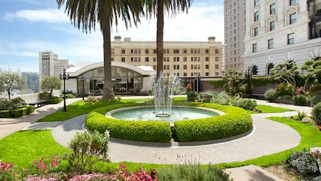 A fountain and palm trees at the entrance to a hotel