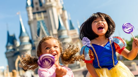 Girls in princess costumes near Cinderella Castle at Magic Kingdom Park in Florida